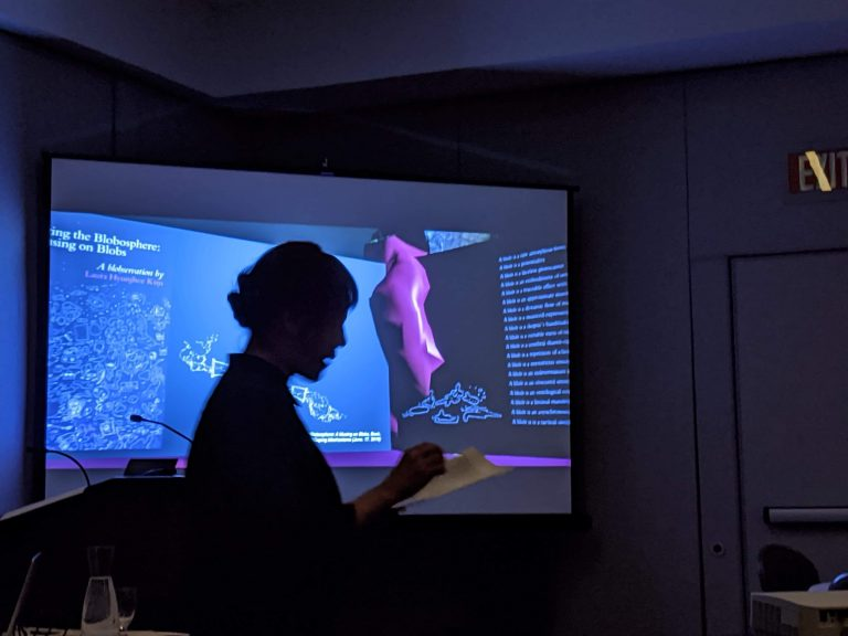 Artsit Laura Hyunjhee Kim stand in front of her presentation at CAA 2020